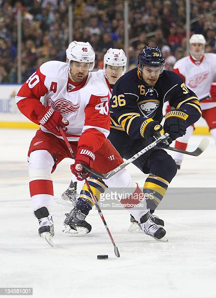 Henrik Zetterberg of the Detroit Red Wings controls the puck and Jiri Hudler trails during their NHL game as Patrick Kaleta of the Buffalo Sabres...