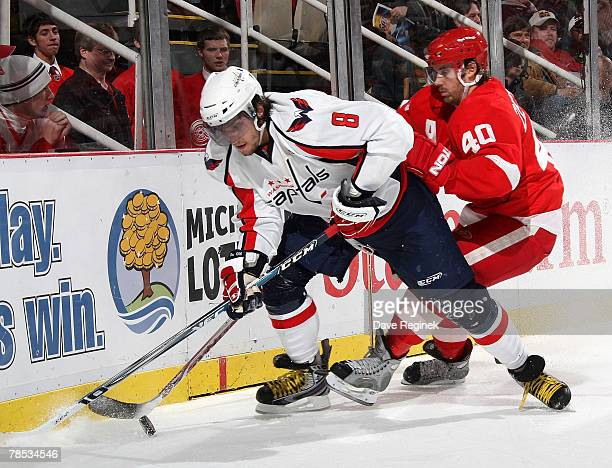 Henrik Zetterberg of the Detroit Red Wings fights for the puck with Alex Ovechkin of the the Washington Capitals during a NHL game on December 17...