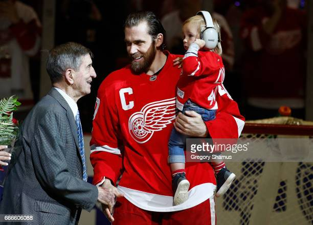 Henrik Zetterberg of the Detroit Red Wings his son Love and Red Wings legend Ted Lindsay during presentation to honor his 1000th NHL game prior to a...