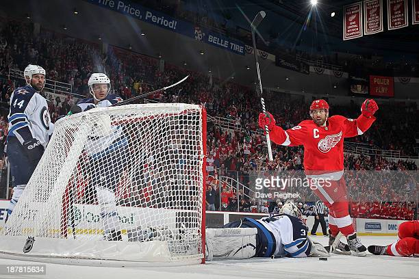 Henrik Zetterberg of the Detroit Red Wings raises his hands after teammate Pavel Datsyuk scores a goal while goalie Ondrej Pavelec of the Winnipeg...