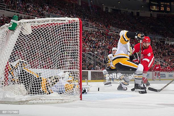 Henrik Zetterberg of the Detroit Red Wings scores a third period goal past the defense of Sidney Crosby and teammate goaltender MarcAndre Fleury of...