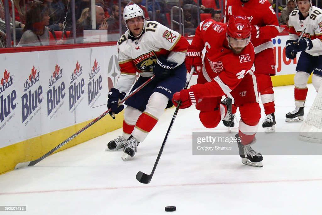 Henrik Zetterberg #40 of the Detroit Red Wings tries to get to the puck in front of Mark Pysyk #13 of the Florida Panthers during the second period at Little Caesars Arena on December 11, 2017 in Detroit, Michigan.
