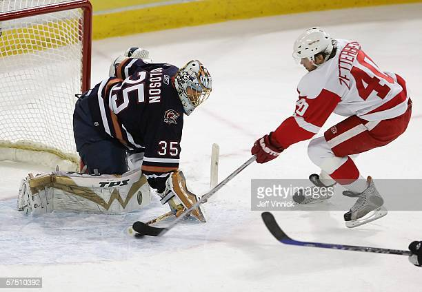 Henrik Zetterberg the Detroit Red Wings shoots past goaltender Dwayne Roloson of the Edmonton Oilers for Detroit's first goal in the first period...