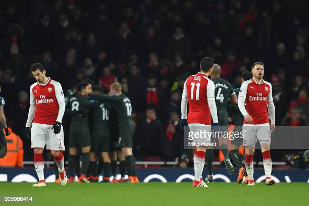 Henrikh Mkhitaryan Mesut Ozil and Aaron Ramsey of Arsenal are dejected after the 2nd Man City goal during the Premier League match between Arsenal...