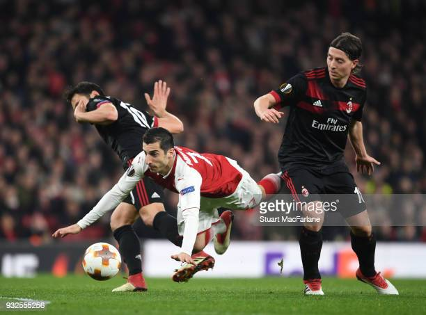 Henrikh Mkhitaryan of Arsenal challenged by Hakan Calhanoglu and Riccardo Montolivo of Milan during UEFA Europa League Round of 16 match between AC...