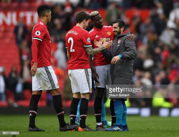 Henrikh Mkhitaryan of Arsenal embraces his former Manchester United teammates Paul Pogba and Victor Lindelof following the Premier League match...