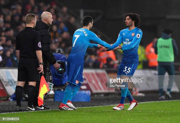 Henrikh Mkhitaryan of Arsenal is being substituted for Mohamed Elneny of Arsenal during the Premier League match between Swansea City and Arsenal at...