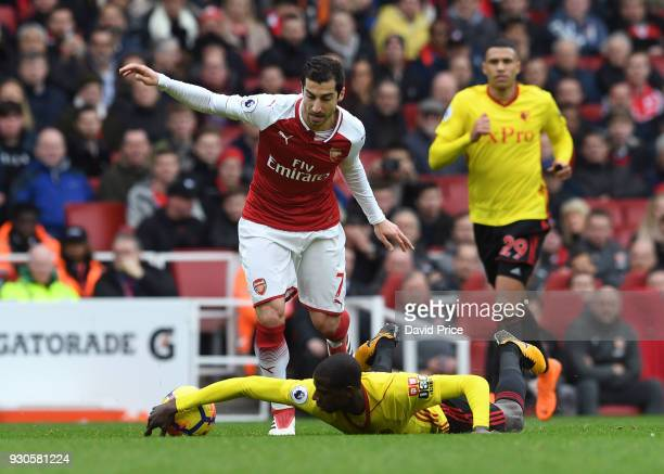 Henrikh Mkhitaryan of Arsenal is challenged by Abdoulaye Doucoure of Watford during the Premier League match between Arsenal and Watford at Emirates...