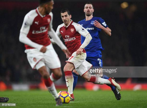 Henrikh Mkhitaryan of Arsenal passes the ball to PierreEmerick Aubameyang to score under pressure from Morgan Schneiderlin of Everton during the...