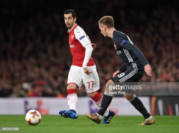 Henrikh Mkhitaryan of Arsenal passes the ball under pressure from Konstantin Kuchaev of CSKA during the UEFA Europa League quarter final leg one...