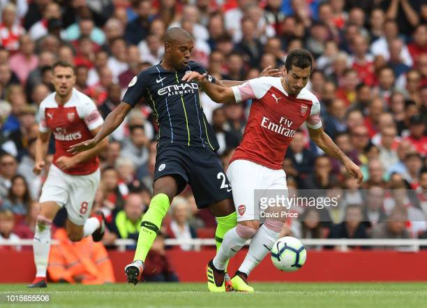 Henrikh Mkhitaryan of Arsenal takes on Fernandinho of Man City during the match the Premier League match between Arsenal FC and Manchester City at...