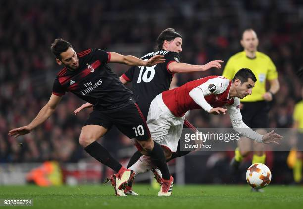 Henrikh Mkhitaryan of Arsenal takes on Hakan Calhanoglu and Riccardo Montolivo of Milan during the match between Arsenal and AC Milan at Emirates...