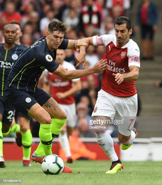 Henrikh Mkhitaryan of Arsenal takes on John Stones of Man City during the match the Premier League match between Arsenal FC and Manchester City at...