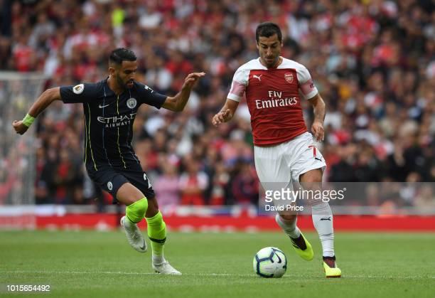 Henrikh Mkhitaryan of Arsenal takes on Riyad Mahrez of Man City during the match the Premier League match between Arsenal FC and Manchester City at...
