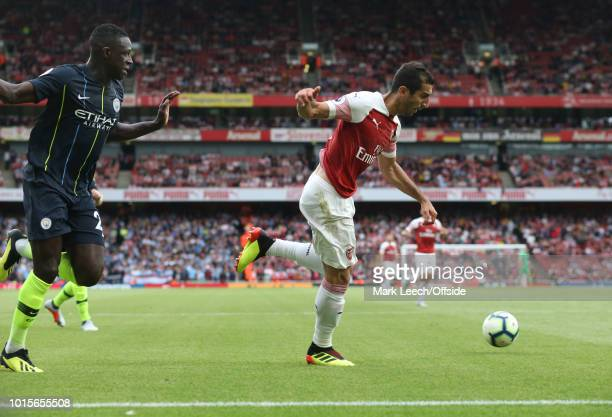 Henrikh Mkhitaryan of Arsenal takes the ball past Benjamin Mendy of Man City during the Premier League match between Arsenal FC and Manchester City...