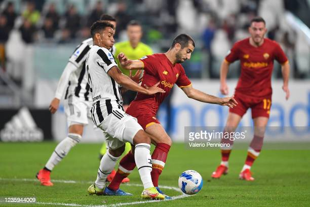 Henrikh Mkhitaryan of AS Roma is challenged by Danilo of Juventus during the Serie A match between Juventus and AS Roma at on October 17, 2021 in...