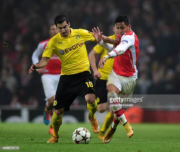 Henrikh Mkhitaryan of Borussia Dortmund and Alexis Sanchez of Arsenal battle for the ball during the UEFA Champions League Group D match between...