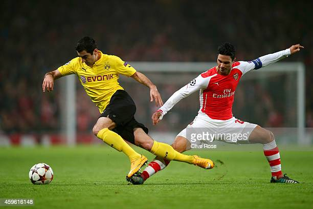 Henrikh Mkhitaryan of Borussia Dortmund is brought down by Mikel Arteta of Arsenal during the UEFA Champions League Group D match between Arsenal and...