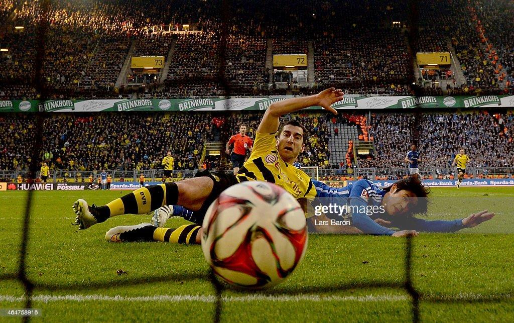 Henrikh Mkhitaryan of Borussia Dortmund scores his teams second goal next to Atsuto Uchida of Schalke 04 during hte Bundesliga match between Borussia Dortmund and FC Schalke 04 at Signal Iduna Park on February 28, 2015 in Dortmund, Germany.