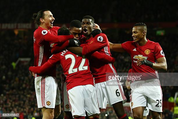 Henrikh Mkhitaryan of Manchester United celebrates with teammates after scoring his team's third goal during the Premier League match between...