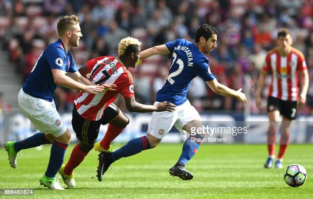 Henrikh Mkhitaryan of Manchester United goes past Didier Ndong of Sunderland and Luke Shaw of Manchester United during the Premier League match...