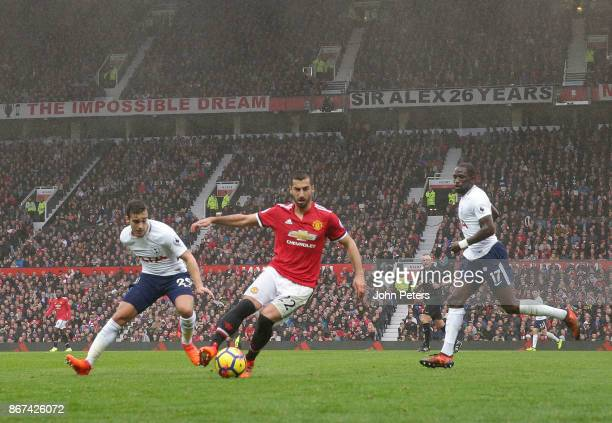 Henrikh Mkhitaryan of Manchester United in action with Harry Winks and Moussa Sissoko of Tottenham Hotspur during the Premier League match between...