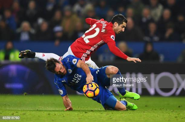 Henrikh Mkhitaryan of Manchester United is challenged by Christian Fuchs of Leicester City during the Premier League match between Leicester City and...