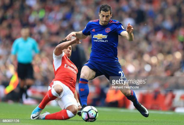 Henrikh Mkhitaryan of Manchester United is tackled by Alex OxladeChamberlain of Arsenal during the Premier League match between Arsenal and...