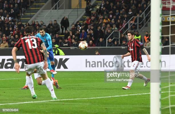 Henrikh Mkhitaryan shoots past AC Milan goalkeeper Gianluigi Donnarumma to score the 1st Arsenal goal during UEFA Europa League Round of 16 match...