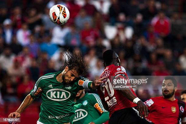Henrique Bauss of Xolos de Tijuana fights for the ball with Duvier Riascos of Palmeiras during a match between Xolos de Tijuana and Palmeiras as part...