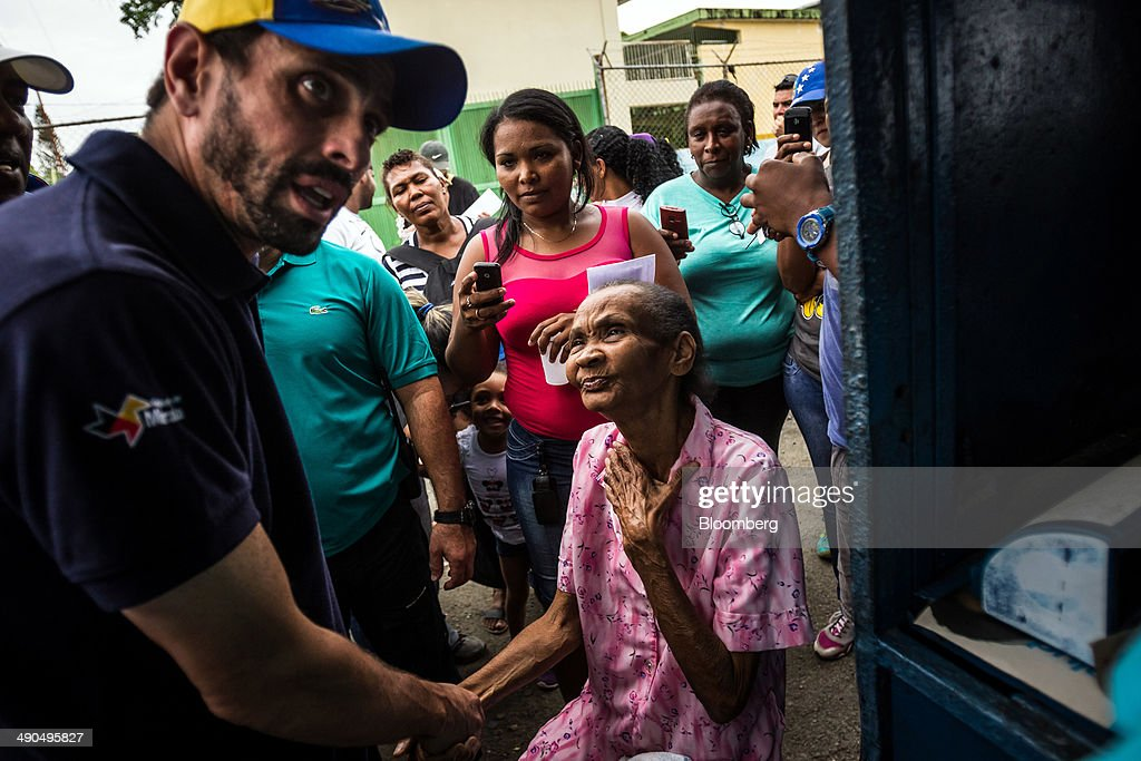 Henrique Capriles, governor of the state of Miranda and a former presidential candidate in the last two elections, left, instructs members of his staff to schedule food deliveries for an elderly woman during a visit to Barlovento, Venezuela, on Saturday, May 10, 2014. Capriles, one of the leaders of the Democratic Unity Roundtable, known as MUD, an alliance which opposes Venezuelan President Nicolas Maduro, said talks with the government scheduled for May 8 were canceled because they 'haven't produced any result up to now.' Photographer: Meridith Kohut/Bloomberg via Getty Images