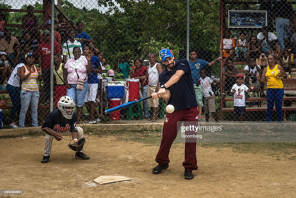 Henrique Capriles, governor of the state of Miranda and a former presidential candidate in the last two elections, plays softball during a visit with constituents in Barlovento, Venezuela, on Saturday, May 10, 2014. Capriles, one of the leaders of the Democratic Unity Roundtable, known as MUD, an alliance which opposes Venezuelan President Nicolas Maduro, said talks with the government scheduled for May 8 were canceled because they 'haven't produced any result up to now.' Photographer: Meridith Kohut/Bloomberg via Getty Images