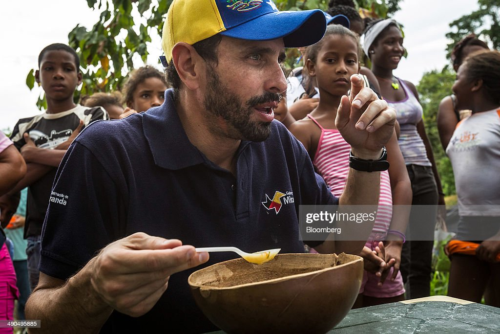 Henrique Capriles, governor of the state of Miranda and a former presidential candidate in the last two elections, eats Sancocho, a traditional chicken stew, while visiting with constituents in Barlovento, Venezuela, on Saturday, May 10, 2014. Capriles, one of the leaders of the Democratic Unity Roundtable, known as MUD, an alliance which opposes Venezuelan President Nicolas Maduro, said talks with the government scheduled for May 8 were canceled because they 'haven't produced any result up to now.' Photographer: Meridith Kohut/Bloomberg via Getty Images