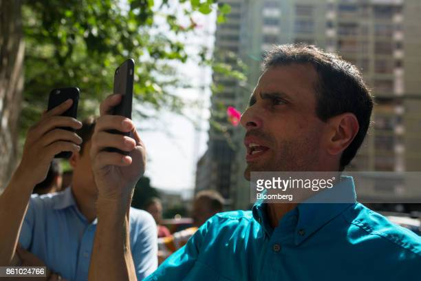 Henrique Capriles opposition leader and former governor of the State of Miranda right uses a smartphone to live stream with periscope the changing of...