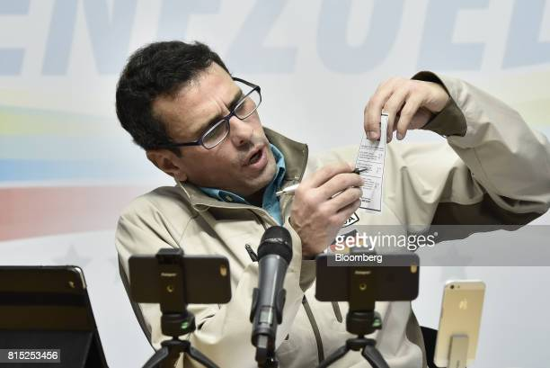 Henrique Capriles opposition leader and governor of the State of Miranda marks a voting card as he speaks during a press conference in Caracas...