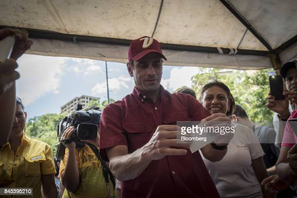 Henrique Capriles opposition leader and governor of the State of Miranda center casts a ballot at a polling station during a primary election in...