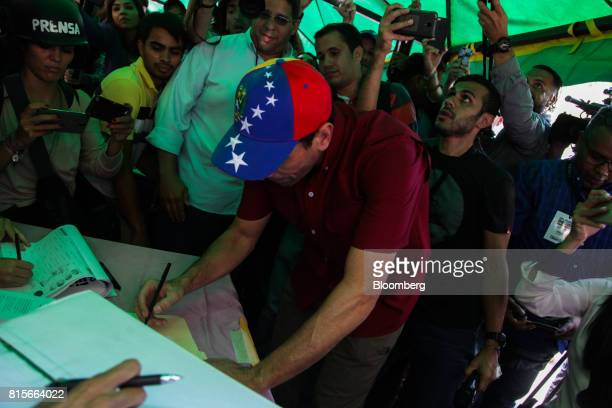 Henrique Capriles opposition leader and governor of the State of Miranda checks in at a polling station to vote during a symbolic plebiscite in...