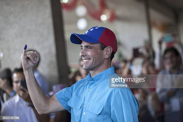 Henrique Capriles opposition leader and governor of the state of Miranda displays his inked finger after voting in the national congressional...