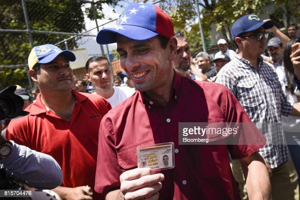 Henrique Capriles opposition leader and governor of the State of Miranda displays his identification while making his way to a polling station during...