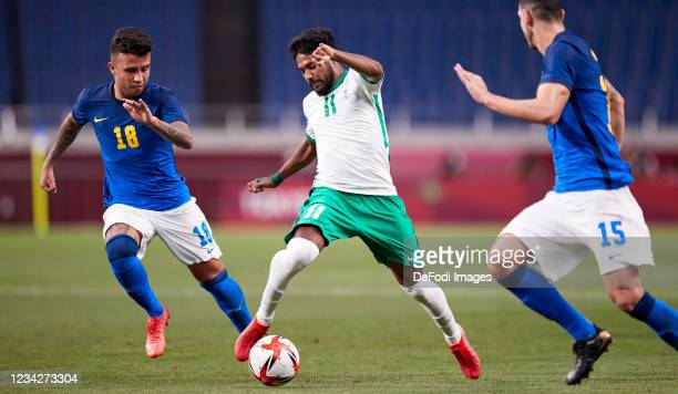 Henrique Matheus of Brazil, Khalid Al-Ghannam of Saudi Arabia and Nino of Brazil battle for the ball during the Men's Group D match between Saudi...