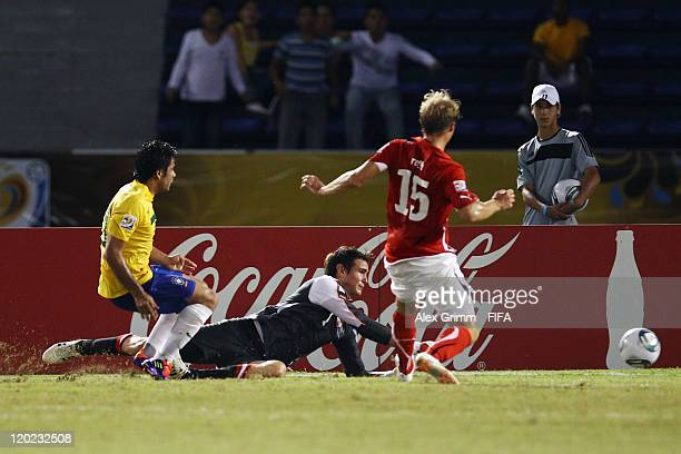 Henrique of Brazil scores his team's first goal against goalkeeper Samuel Radlinger and Lukas Rath of Austria during the FIFA U20 World Cup Group E...