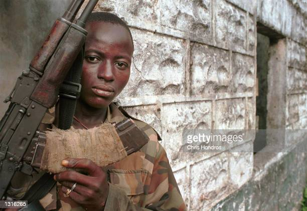 Henry a teenaged Revolutionary United Force rebel solider brandishes his weapon June 9 2001 in the town of Koindu Sierra Leone The RUF infamous for...