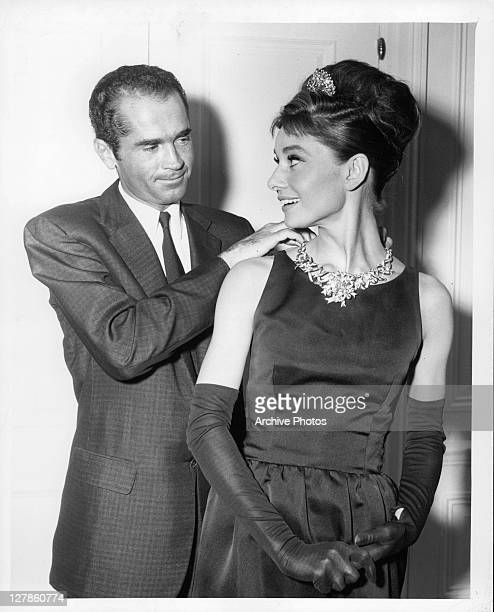 Henry B Platt, great-grandson of the founder of Tiffany's, adjusts Audrey Hepburn's necklace to signal the start of production for the film...