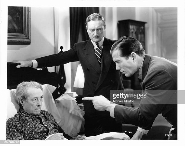 Henry B Walthall is questioned by Nat Pendleton as Edmund Lowe watches in a scene from the film 'The Garden Murder Case' 1936