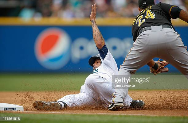 Henry Blanco of the Seattle Mariners slides into third base from first on a single by teammate Nick Franklin against third baseman Pedro Alvarez of...