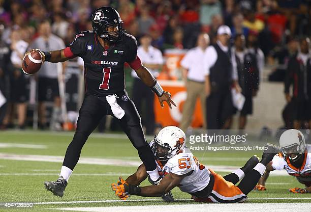 Henry Burris of the Ottawa Redblacks avoids getting sacked by Alex Bazzie of the BC Lions during a CFL game at TD Place Stadium on September 5 2014...
