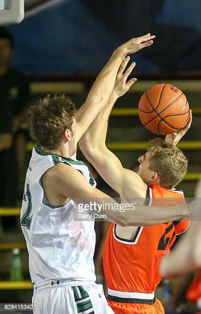 Henry Caruso of the Princeton Tigers tries to shoot over Jack Purchase of the Hawaii Rainbow Warriors during the first half of the Pearl Harbor...