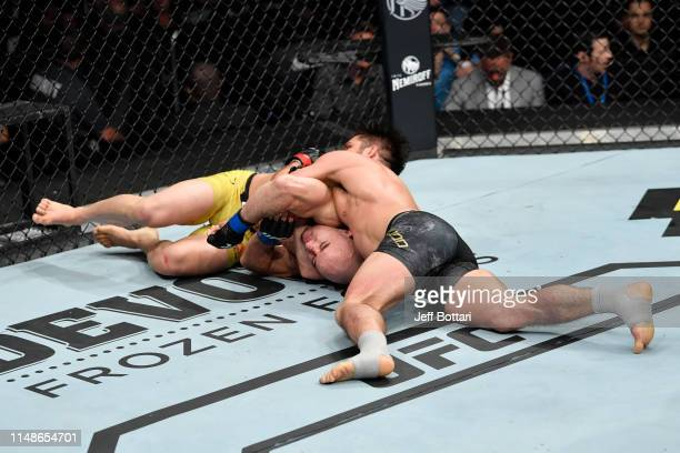 Henry Cejudo attempts to submit Marlon Moraes of Brazil in their bantamweight championship bout during the UFC 238 event at the United Center on June...