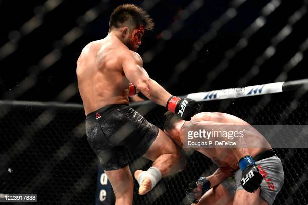 Henry Cejudo of the United States knees Dominick Cruz of the United States in their bantamweight title fight during UFC 249 at VyStar Veterans...