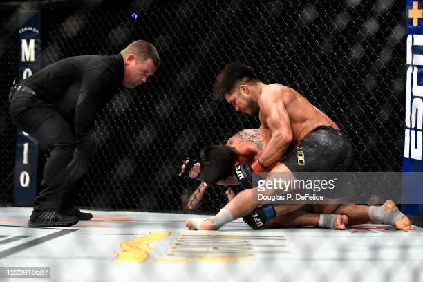 Henry Cejudo of the United States punches Dominick Cruz of the United States on the ground in their bantamweight title fight during UFC 249 at VyStar...